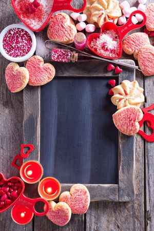copy space: Valentines day cookies and decorations around a chalkboard copy space