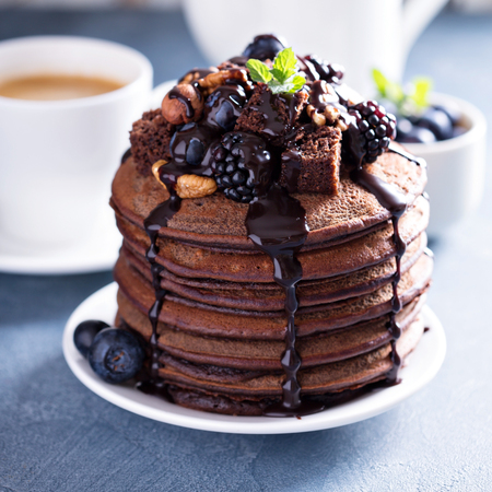 toppings: Stack of chocolate pancakes with sauce and toppings