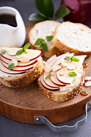 Small crostini with ricotta and apple on cutting board