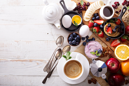 Colorful and tasty breakfast ingredients on white table