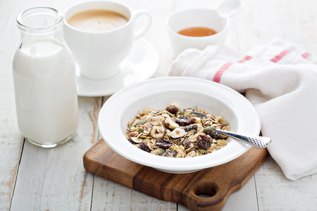 Muesli with nuts and dried fruits served with honey and milk