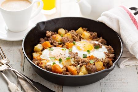 Aardappel en zoete aardappel hash met eieren in gietijzeren pan Stockfoto