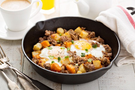 hash: Potato and sweet potato hash with eggs in cast iron pan