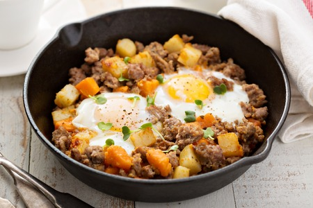 Kartoffel und Süßkartoffel-Hash mit Eiern in Pfanne aus Gusseisen Standard-Bild - 51701564