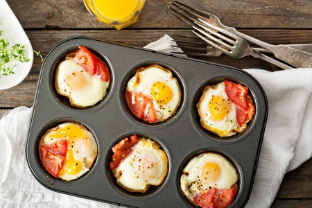 breakfast eggs: Baked eggs with ham and tomato in maffin tin Stock Photo