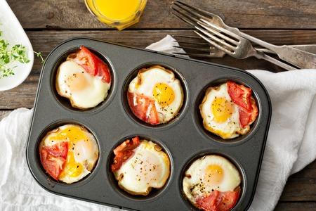 Sült tojás sonkával és paradicsommal maffin ón Stock fotó