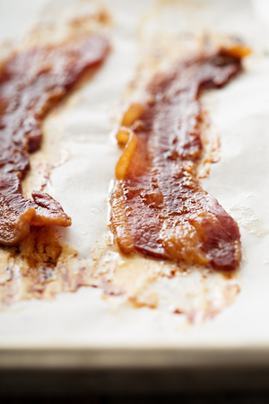 sizzling: Sizzling hot bacon pieces on a baking sheet
