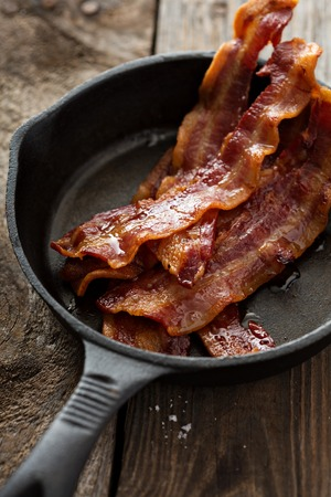 sizzling: Sizzling hot bacon pieces in a cast iron skillet