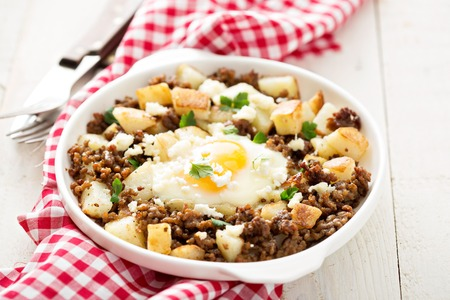 hashbrown: Potato hash with sausage and fried egg in a baking dish Stock Photo