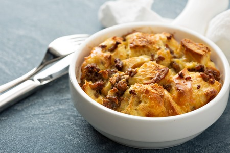 Breakfast strata with cheese and sausage in small baking dish