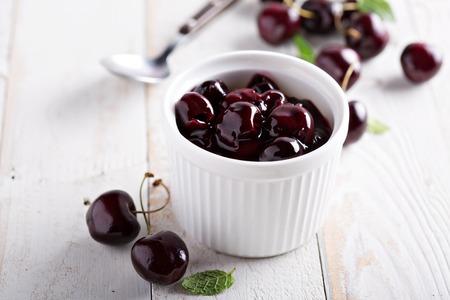 ramekin: Homemade cherry sauce in white ramekin made from sweet cherry
