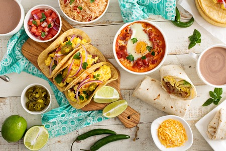 Variety of colorful mexican cuisine breakfast dishes on a table
