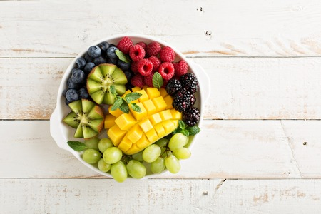 fruta tropical: Plato de frutas con variedad de bayas, mango y kiwi Foto de archivo