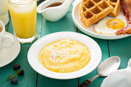 grits: Cheesy grits with butter in a white bowl for breakfast