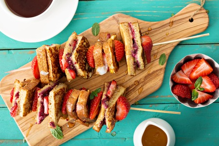 French toast pieces with jam and peanut butter on a skewer with strawberry