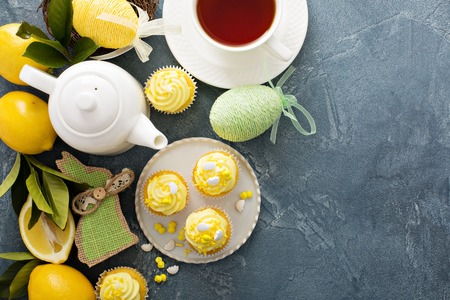 Easter background with lemon cupcakes for Easter brunch with yellow frosting and sprinkles