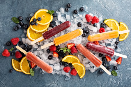 Variety of healthy ice popsicles with fruits and berries on ice