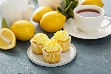 Lemon cupcakes with bright yellow frosting and sprinkles Фото со стока