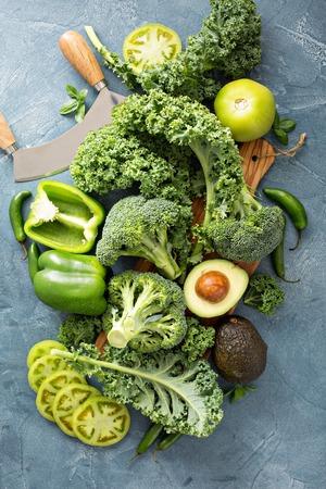 Verschiedene grüne Gemüse auf dem Tisch, einschließlich Grünkohl, Brokkoli und Avocado