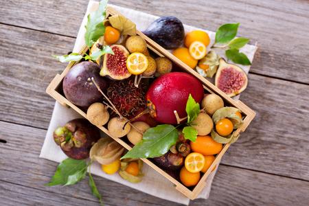 Les fruits exotiques dans une caisse avec kumquats et les figues