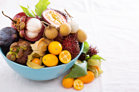 Exotic fruits on white  with kumquats and figs Stock Photo