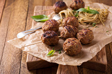 cooked pepper ball: Turkey meatballs on wooden skewers with pesto pasta