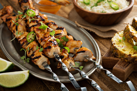 Chicken kabobs with sweet and sour sauce on metal skewers Banco de Imagens - 56946926