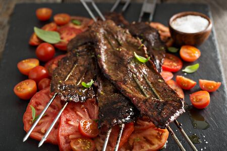 flank: Flank steak on skewers with tomato salad