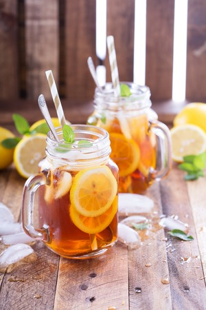 Iced tea with lemon slices and mint on rustic background Фото со стока