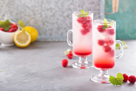 Pink refreshing cold raspberry lemonade in tall glasses 스톡 콘텐츠