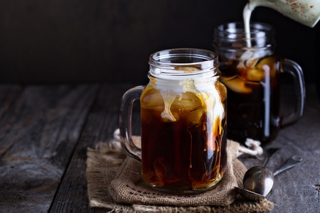 Iced coffee with milk in mason jars  on the table Stok Fotoğraf - 56951894