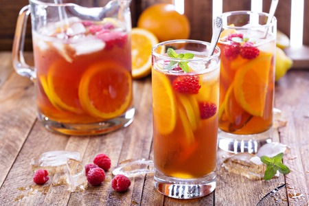 Iced tea with orange and raspberry in tall glasses on rustic background Stock Photo