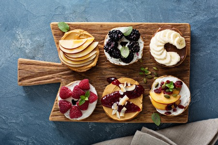copy paste: Variety of bagels with different toppings for breakfast on a board