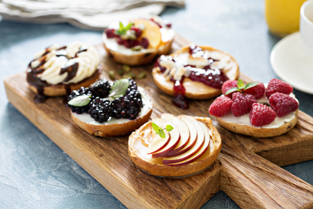 toppings: Variety of bagels with different toppings for breakfast on a board