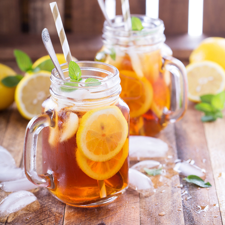 Iced thee met schijfjes citroen en munt op rustieke achtergrond