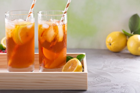 Iced tea variety in tall glasses on green background