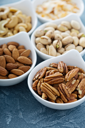 pine kernels: Variety of nuts in small white bowls healthy snacks