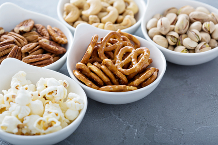 Variety of healthy snacks in white bowls pretzels and nuts Imagens - 58898039