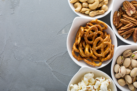 bowls of popcorn: Variety of healthy snacks in white bowls pretzels and nuts