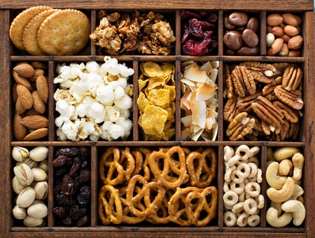 Variety of healthy snacks overhead shotin a wooden box