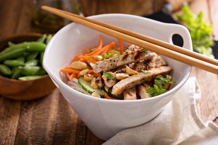 Asian cuisine chicken salad with rice noodles, carrot and peanuts