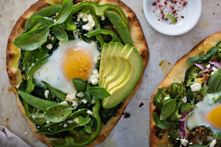 Breakfast pizza on pita with baked egg, spinach and green vegetables Stok Fotoğraf - 59100131