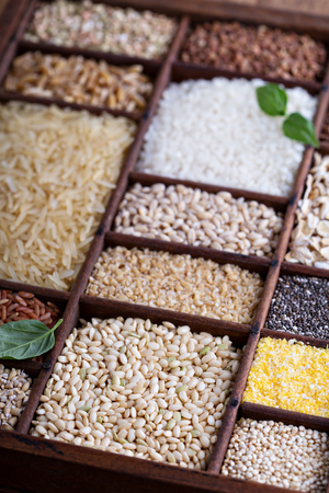 Variety of healthy grains and seeds in a wooden box mostly gluten free with rice, quinoa and buckwheat Stockfoto