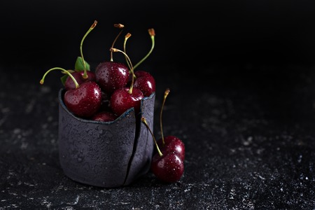 Fresh sweet cherries in handmade black ceramic cup dark low key photo Stock Photo
