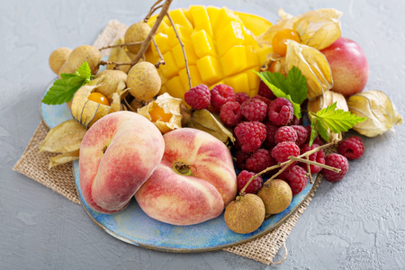Fresh and ripe tropical fruit board including mango,longan and peaches