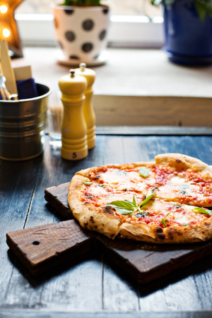Pizza Margherita with mozzarella and fresh basil freshly baked on a table in cafe