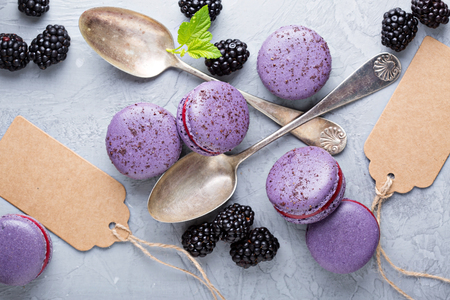 French macarons with berry filling on a gray table