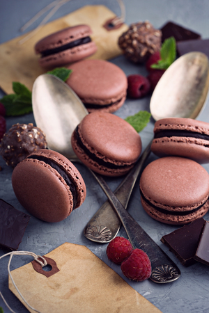 ganache: Chocolate french macarons with ganache filling on a gray table Stock Photo