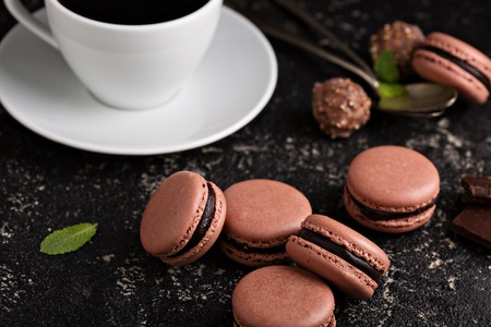 ganache: Chocolate french macarons with ganache filling on a black table with coffee