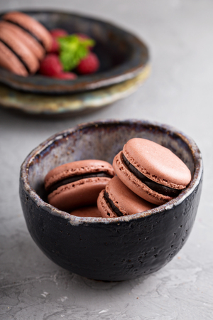filling in: Chocolate french macarons with ganache filling in a black bowl
